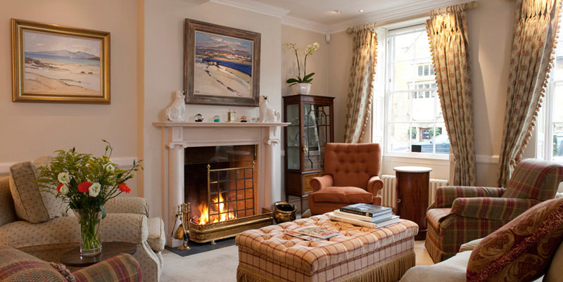 The cosy sitting room that guests get exculsive access to, lit by a roaring fire.