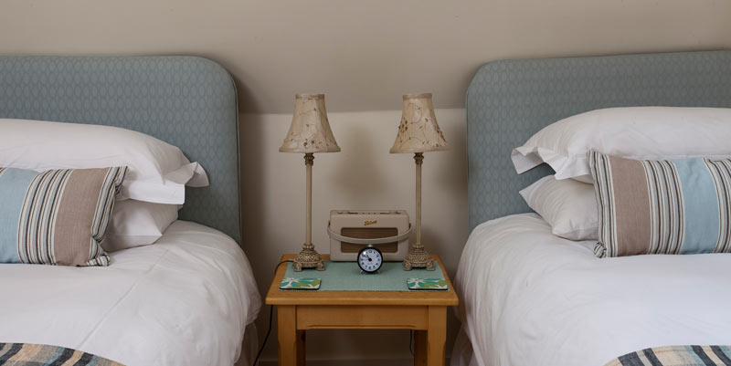 Two beds and the bedside table in the spacious and well lit twin room.